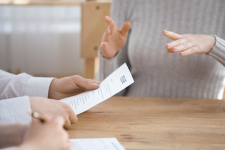 Close up of HR managers read candidate resume considering her candidature for open position, confident work applicant gesture talking with recruiters at business interview. Employment concept Stock Photo