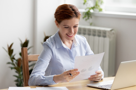 Happy businesswoman sitting at desk looking income chart shown on paper feels satisfied. Executive manager analyzing sales statistics report. Company growth, profit increase success at work concept Banco de Imagens