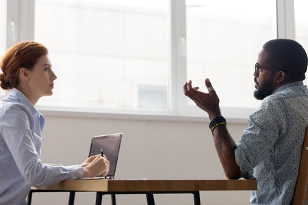 Diverse multiracial businesspeople sitting at desk in boardroom negotiating, executive manager interviewing black job candidate side view. Company representative listen client during business meeting