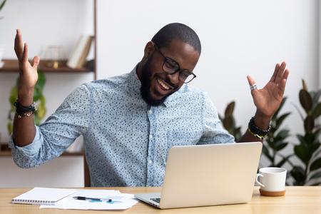 Vrolijke zwarte zakenman zittend aan een bureau kijkend naar computerscherm praten met vriend informeel videogesprek voeren. Afrikaanse werknemer ontving geweldig nieuws lees e-mail voelt zich blij om beloning of promotie te krijgen