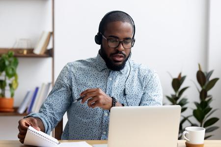Hombre joven negro sentado en la mesa con audífonos aprender un idioma extranjero mejora el conocimiento mirando la pantalla de la PC escuchando una lección de audio sosteniendo el bolígrafo y el bloc de notas hace algunas notas. Concepto de e-learning