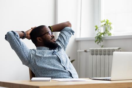 Schwarzafrikanischer tausendjähriger Geschäftsmann macht während des Arbeitstages Pause, entspanntes Sitzen auf einem Stuhl am Schreibtisch, hält die Hände hinter dem Kopf und schaut auf das Fenster Denken fühlt sich gut an. Tagtraumkonzept zum Stressabbau Standard-Bild