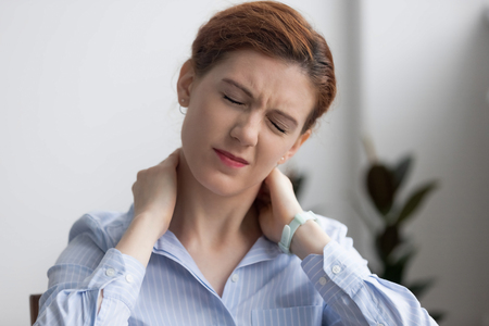 Head shot woman writhing in pain suffering from neck pain at work in office. Fatigued female touching massaging sore neck feels unhealthy. Sedentary lifestyle, long time working without break concept