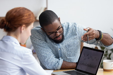Diverse millennial colleagues working together analyzing diagram looking at computer screen. Black mentor helps female apprentice understand corporate program explaining interface showing on monitor Stock Photo