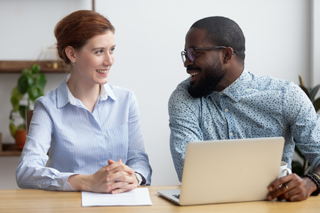 Diverse businesspeople client and consultant sitting at desk during business meeting. Mentor and employee use pc look at each other talking black colleague helps intern understand corporate program Stock Photo
