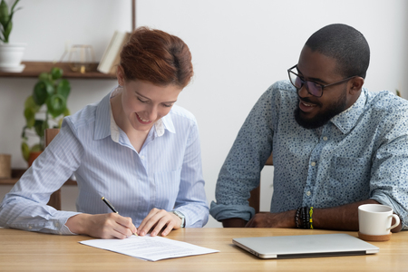 Young attractive woman candidate sitting at desk with black company executive manager getting hired signing job contract feels happy. Satisfied client affirming selling or buying agreement at agency