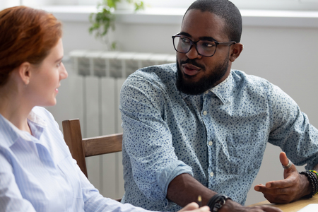 Diverse business people sitting at desk during meeting, black company owner talking with female investor discuss startup business plan. Multiracial colleagues take break having informal conversation 写真素材 - 114277983
