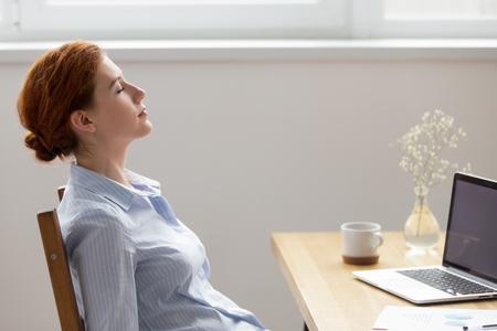Seitenansicht junge ruhige Frau sitzt am Schreibtisch am Arbeitsplatz gegenüber dem Computer mit geschlossenen Augen träumend frische Luft atmen. Nach Beendigung der Arbeit zufriedene Geschäftsfrau, die sich entspannt ausruht, fühlt sich gut an