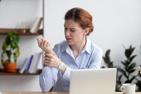 Imprenditrice seduto alla scrivania in ufficio tocco il polso sente dolore. Donna malsana turbata con sindrome del tunnel carpale a causa dell'uso attivo ea lungo termine della tastiera e del mouse nella postura sbagliata