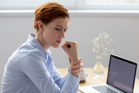 Businesswoman sitting at desk opposite pc suffers from pain in hand while working in office. Young female massaging wrist having carpal tunnel syndrome, caused by long-term use of keyboard and mouse