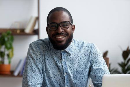 Kopfschussporträt eines positiven afroamerikanischen Geschäftsmannes in Brillen, der am Schreibtisch mit Laptop sitzt. Selbstbewusst glücklich mit einem arglosen Lächeln, das Unternehmer in die Kamera schaut, die am Arbeitsplatz posiert