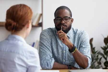 Diverse business people sitting in office, black ceo interviewing female for company position feel doubts that candidate meets requirements. Bad first impression and unsuccessful job interview concept