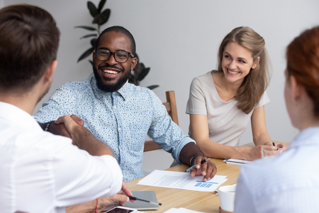 Millennial successful multiracial business people gathered together for startup discussion, black african investor shaking hands with executive company manager greeting each other laughing handshaking