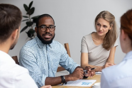 Diverse multinational young professional millennial company members gathered together in office boardroom listening with distrust black african speaker presenting sharing new creative ideas and plans