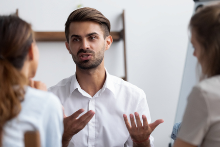 Millennial confident male worker express his opinion about business plan share thoughts with rear view female colleagues. Candidate for job vacancy answering on HR managers questions during interview