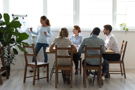 Five businesspeople gathered together for business training attentive listening mixed race coach. Company member prepared financial report in charts diagrams on increasing profits and reducing costs Imagens - 114278066