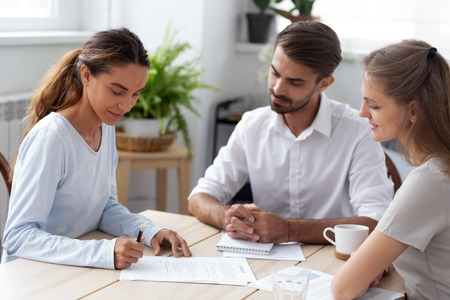 Mixed race client hold pen put signature at official paper make buy or sell deal sitting with partners during meeting. After successful job interview millennial woman signing employment agreement Stock Photo