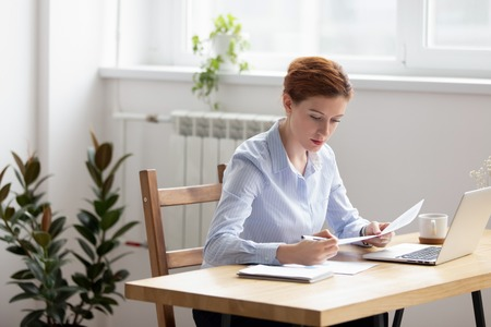 Concentrated serious businesswoman sitting at desk holding documents checking analyzing data, sales statistics doing paperwork. Confident company executive manager preparing report for conference