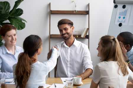 Successful businesspeople gathered together in office boardroom for negotiate and discuss new project greeting shaking hands. Company executive manager welcoming newcomer new worker female handshaking