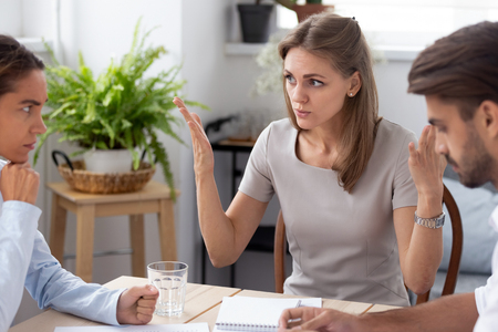 Dissatisfied team leader talking with colleagues discussing failure in work,  coworkers having different opinion sitting together in office arguing disputing blond colleague insists on her point of view Stock Photo