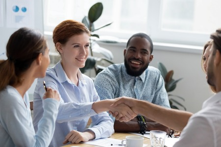 Businesswoman company executive manager sitting with colleagues handshaking with client gathered together in boardroom. Business people welcoming experienced business coach starting seminar training
