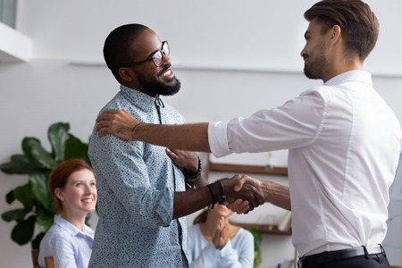 Diverse people gathered in meeting executive manager shake hands with black employee impressed by professionalism for leadership qualities creative solutions and efforts rewarding him for amazing work. Stock Photo