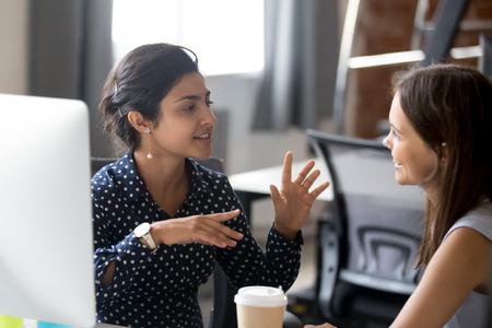 Freundliche Kolleginnen mit guten Beziehungen, angenehme Konversation am Arbeitsplatz während der Kaffeepause, lächelnde junge Frau hört gesprächige Mitarbeiter, bespricht neues Projekt, redet im Büro