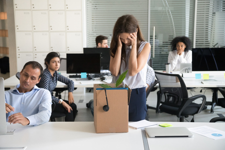 Desperate dismissed woman holding head in hands at workplace, upset female employee pack belongings in cardboard box, feeling stressed about job loss, unexpected undeserved dismissal, discrimination
