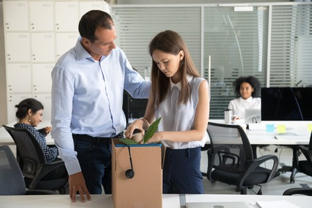 Colleague businessman supporting dismissal upset woman pack belongings in cardboard box, preparing to leave office, sad female office worker despair, feeling stressed about job loss, last day at work