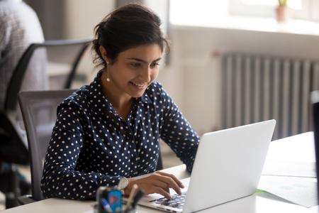 Sorridente dipendente indiana che utilizza il computer portatile sul posto di lavoro, guardando lo schermo, donna d'affari concentrata che prepara un rapporto economico, lavorando su un progetto online, stagista allegro che lavora al computer, digitando