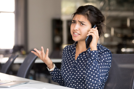 Outraged attractive Indian female employee talking by phone, arguing with client or customer, actively gesticulating, businesswoman having serious conversation on smartphone, solve business problem