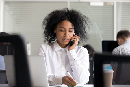 Focused African American woman making notes on sticker, clarifies information, talking on phone, registers complaint from client or customer, female employee consulting by mobile device at workplace