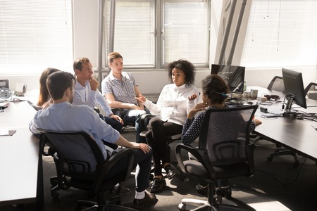 Serious African American female leader, coach talking with employees at company meeting, boss discussing business strategy, plan with multiracial team office workers, giving instructions, report news