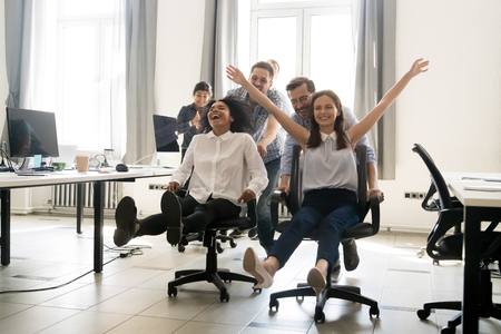 Happy multiracial colleagues group having fun together, riding on chairs in office, diverse excited office workers enjoying break, laughing, engaged funny activity, celebrating corporate success Imagens