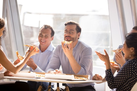 Businessman enjoying pizza with friendly colleagues, diverse employees team eating Italian food together, talking laughing, having fun at work, good relations, sharing meal at lunch break