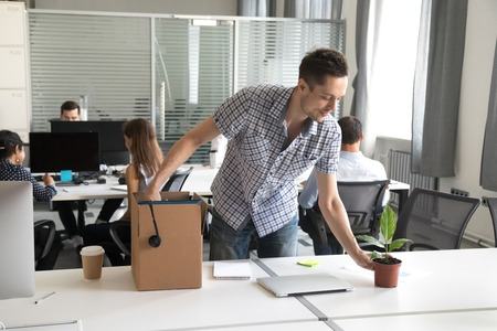 Happy young man, intern unpack cardboard box with belongings at workplace, starting work in new company, first day of job, prepare to beginning of working day, newly hired office worker, newcomer Stock Photo - 114278001