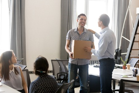 Boss introducing just hired male employee holding cardboard box with belongings in hands, first day at work, team welcoming new member, newcomer, getting acquainted with happy coworker