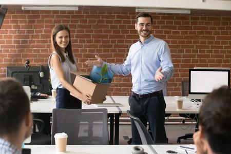 Líder de la compañía emocionado presentando empleada contratada sosteniendo una caja de cartón con pertenencias en las manos, equipo con ceo dando la bienvenida a nuevo miembro, recién llegado, primer día de trabajo, concepto de introducción
