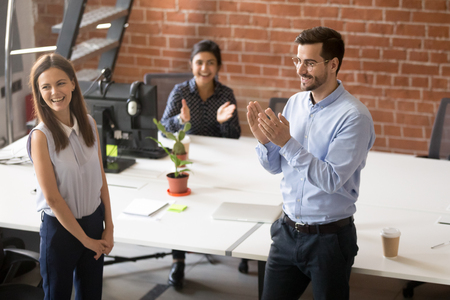 Friendly team leader, boss introducing to colleagues hired new member of team, newcomer, applauding to female employee, congratulating office worker with promotion, business success, reward