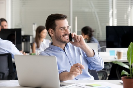 Smiling friendly man talking on phone in office, having pleasant conversation with client or customer, receiving good news or offer, marketing manager making business call, chatting with friend Stock fotó