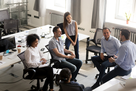 Smiling diversity team of employees, interns sitting circle, listening to business coach on training, trainer, discussing business strategy, plan with male leader, involved in team building activity Stock Photo