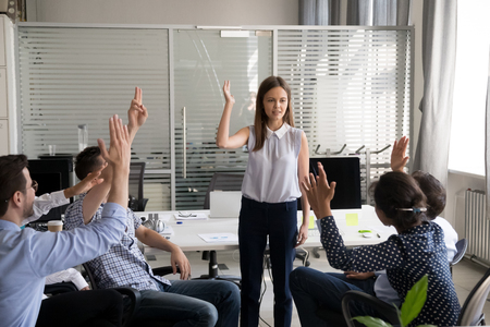 Young female mentor, coach holding training for office workers group, employees raised hands taking part in team building activity, interns, colleagues show activity at answering leader question Stock Photo