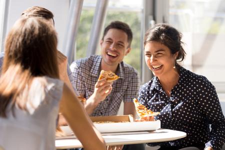 Indiase opgewonden vrouw lachen om grappige grap, pizza eten met diverse collega's op kantoor, gelukkige multi-etnische medewerkers die samen plezier hebben tijdens de lunch, genieten van een goed gesprek, emoties Stockfoto