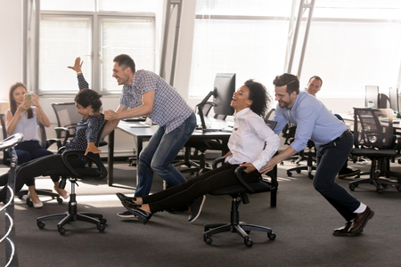 Excited diverse employees having fun together in office, riding on chairs at work, enjoying break, laughing, colleagues shoot video on phone, engaged funny activity, celebrating corporate success Stock Photo