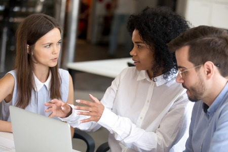 Diverse employees discussing online project with African American leader, working together on computer project, businesswoman, intern with female boss, mentor talking about business strategy, instruct