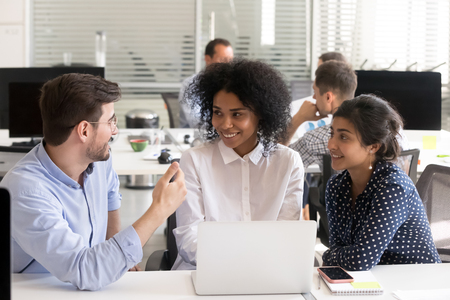 Diverse multiracial colleagues discussing online project at workplace, male coach, mentor give instructions, talking with African American and Indian female interns, office workers, good conversation Stockfoto