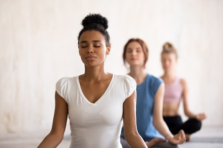 Group diverse young beautiful women sitting in lotus position meditating during session at yoga studio. Girls practising exercises visualizing calming the brain increasing awareness and attentiveness 스톡 콘텐츠