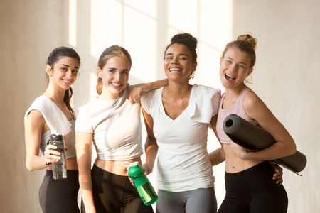 Indian biracial and caucasian beautiful women standing together smiling looking at camera girls drinking water after power training or yoga session feels happy and satisfied. Healthy lifestyle concept Stock Photo