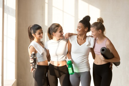 Diverse multi-ethnic slim women friends talking after workout resting standing in yoga class. Attractive girls looks perfect and healthy feels happy and satisfied after intense training in sport club Stock Photo