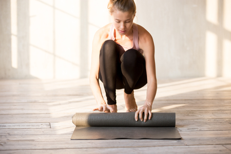 Female wearing sportswear ready for sports activities unrolling yoga mat before workout exercise. Young woman folding rubber carpet finishing training at gym. Healthy lifestyle and body care concept